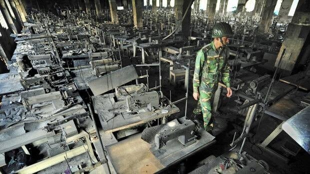 A Bangladeshi police officer walks between rows of burnt sewing machines in a garment factory outside Dhaka, Bangladesh. The factory lost its safety clearance months before 112 people were killed in a blaze there.