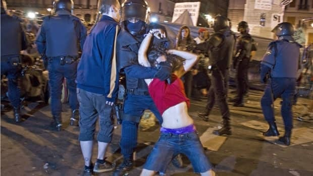 A young woman is pulled away from Madrid's Puerta del Sol plaza last week as police broke up protests against austerity and unemployment that has hit one out of every four citizens in Spain.