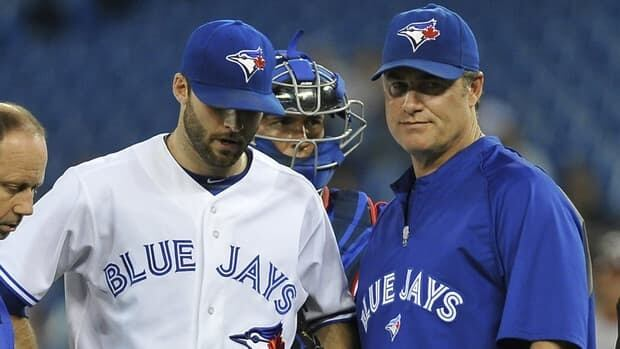 Brandon Morrow, left, of the Toronto Blue Jays leaves the game against the Washington Nationals in the first inning due to injury as manager John Farrell looks on.