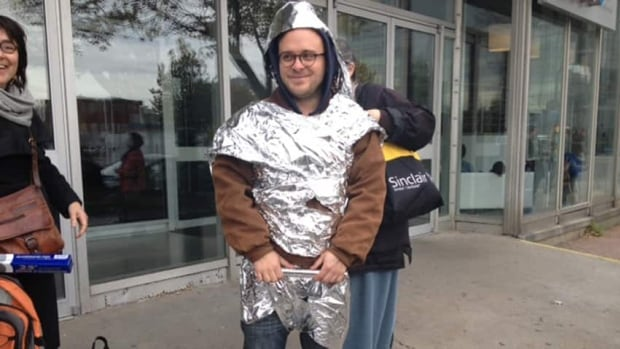 A man dressed in tinfoil demonstrates outside the Quebec rental board office to draw attentoin to tenant complaints surrounding heating issues.