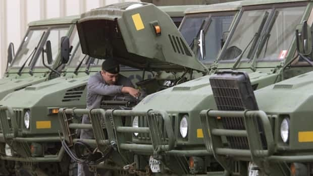 A vehicle technician makes some adjustments to a truck at Canadian Forces Base Edmonton. A program to buy 1,500 new combat trucks was cancelled at the last minute because the military wanted to spend 300 million dollars more than had been approved.