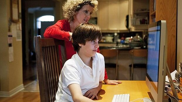 Dylan Roberts, who attends the French high school Monseigneur de Charbonnel, poses for a photo as he works on the computer with his mother Lynda Rinkenbach at their Toronto home. THE CANADIAN PRESS/Michelle Siu