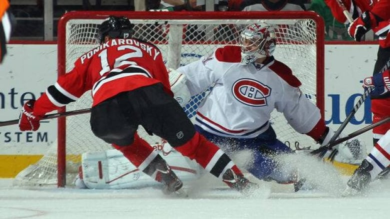 3eb530dba88 Carey Price of the Montreal Canadiens, right, covers the net against the New  Jersey Devils at the Prudential Center on February 2, 2012 in Newark, ...