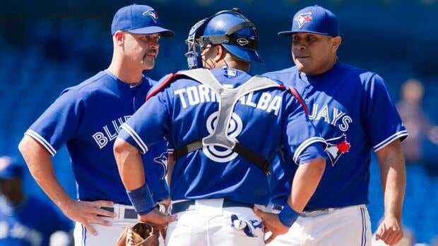 Toronto Blue Jays starting pitcher Ricky Romero (right) reacts as he is spoken to on the mound by coach Pete Walker (left) as he stands on the mound with catcher Yorvit Torrealba during the second inning against the Tampa Bay Rays in Toronto on Sunday.