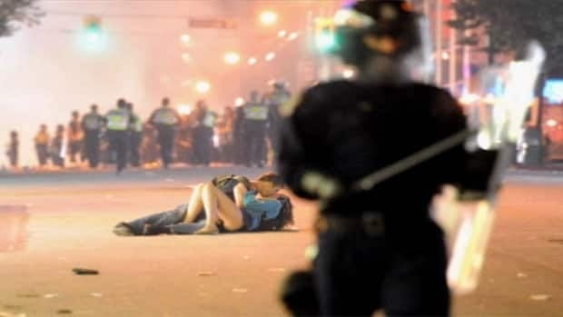 Photographer Rich Lam was caught up in a crowd being pushed back by riot police when he looked up a street and saw the 'kissing couple.'