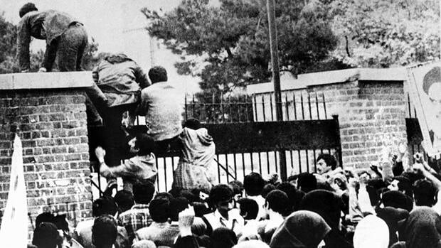 Iranian students climb over the wall of the U.S. Embassy in Tehran on Nov. 4, 1979.