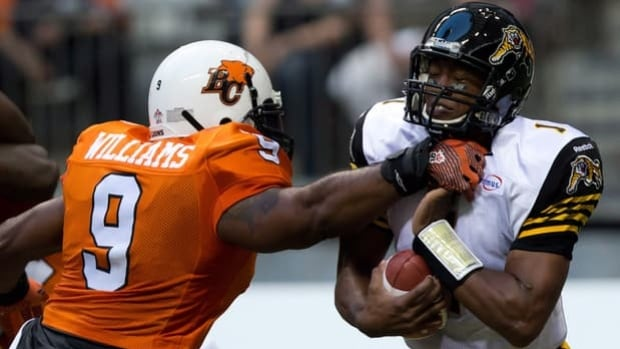 Henry Burris, right, of the Ticats is tackled by Keron Williams in a 39-36 loss at B.C. on July 6.