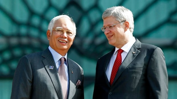 Prime Minister Stephen Harper, right, poses with his Malaysian counterpart Najib Razak after Sunday's announcement that Malaysia's state-owned oil company, Petronas, will invest billions in Canadian liquefied natural gas development.