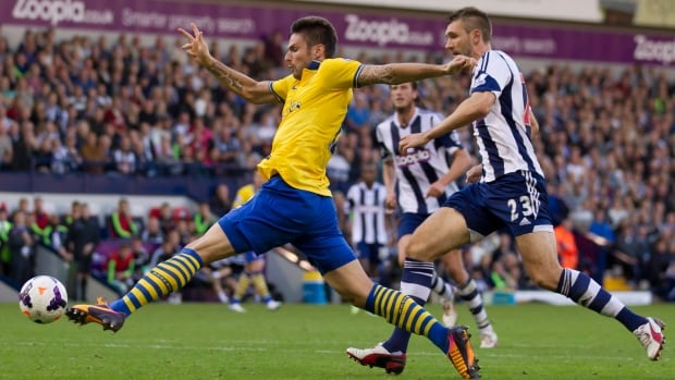 Arsenal's Olivier Giroud, left, beats West Bromwich Albion's Gareth McAuley to the ball during their match at The Hawthorns Stadium, West Bromwich, England on Sunday.