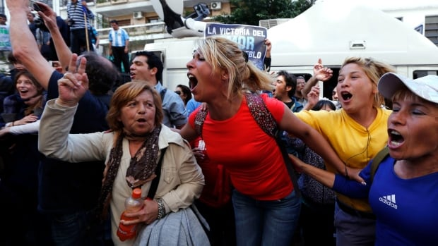Supporters of Argentine President Cristina Fernandez react outside a hospital in Buenos Aires on Tuesday after the announcement that her brain surgery was successful.