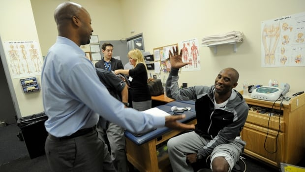 Kobe Bryant of the Los Angeles Lakers greets Denver Nuggets coach Brian Shaw on Tuesday at Citizens Business Bank Arena. Bryant's rehab from a torn Achilles tendon is progressing well and the all-star guard is expected to be a few weeks away.