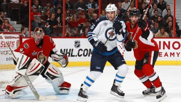 Jets captain Andrew Ladd (16) positions himself between netminder Craig Anderson and defenceman Jared Cowen on Oct. 20.