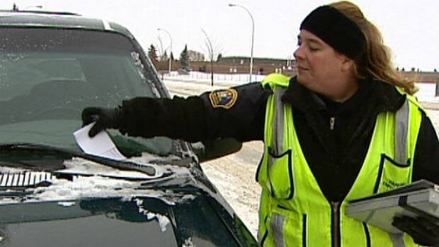 An Edmonton bylaw enforcement officer issues a ticket to a truck parked on a bus route Friday morning.