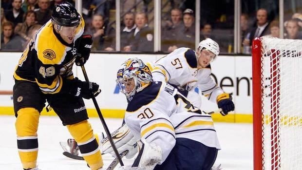 Boston Bruins' Rich Peverley, right, scores on Buffalo Sabres goalie Ryan Miller, left, in the second period of the Bruins's 6-2 victory.