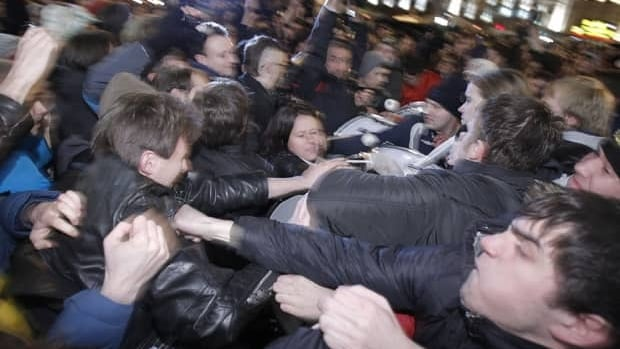 Opposition activists, left, and members of pro-Kremlin youth movements scuffle during demonstrations in Triumphal Square in Moscow on Tuesday.