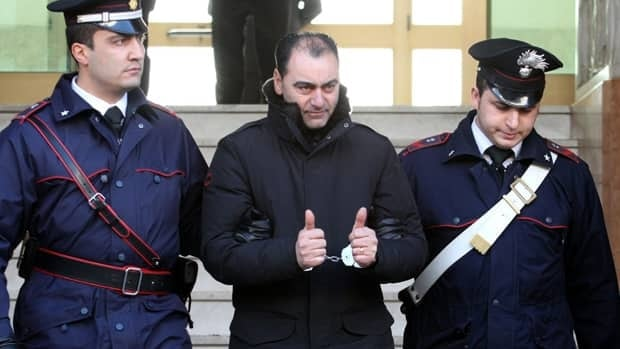 A man identified as Giovanni Pronesti, an alleged member of the 'ndrangheta crime syndicate, is escorted by police officers in Italy on Tuesday. Italian police were conducting a major crackdown Tuesday against the 'ndrangheta crime syndicate, with suspects also being sought in Thunder Bay, Ont., and Toronto.