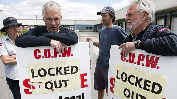 Locked out Canada Post employees stand outside a postal facility in Dartmouth, N.S. on Wednesday. No new talks are planned between Canada Post and the union, as the government attempts to pass a back-to-work a bill that would force each side to submit a final offer to an arbitrator.