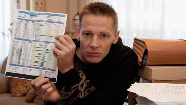 Former soldier Pascal Lacoste holds up a copy of a test that shows a high level of uranium in his system at his home in Quebec City.