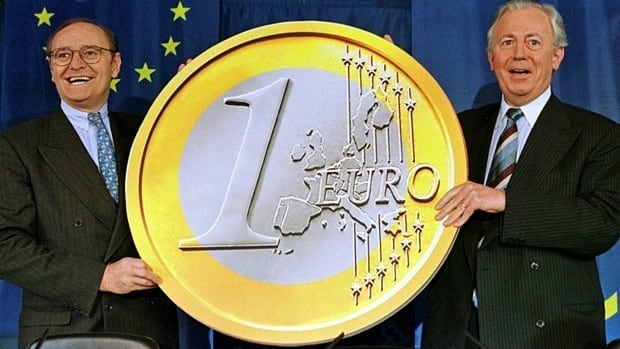 Then European monetary affairs commissioner Yves-Thibault de Silguy, left, and president of the European Commission Jacques Santer hold a model of a euro coin prior to a news conference in Brussels on May 1, 1998. The euro was introduced as a unit of accounting a year later; bills and coins began circulating in 2002.