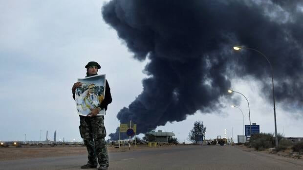 A pro-Gadhafi fighter holds a poster of Libyan Leader Moammar Gadhafi as smoke rises from the burning oil refinery in Ras Lanouf, Libya on March 12. Oil prices climbed Monday as traders prepare for prolonged fighting in the country.