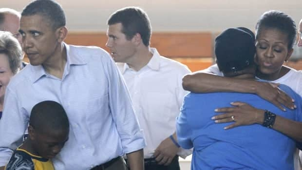 U.S. first lady Michelle Obama hugs at right as she and President Barack Obama visit residents at a rally point at Holt Elementary School in Holt, Ala., Friday.