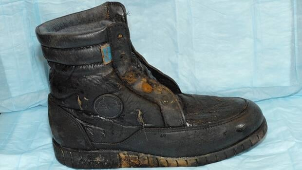 The BC Coroners Service released this photo of a hiking boot that washed up on the shore of Sasamat Lake on Nov. 5. The boot is a black Cougar-brand men's size 12 with a blue felt lining. The metal eyelets are significantly rusted.
