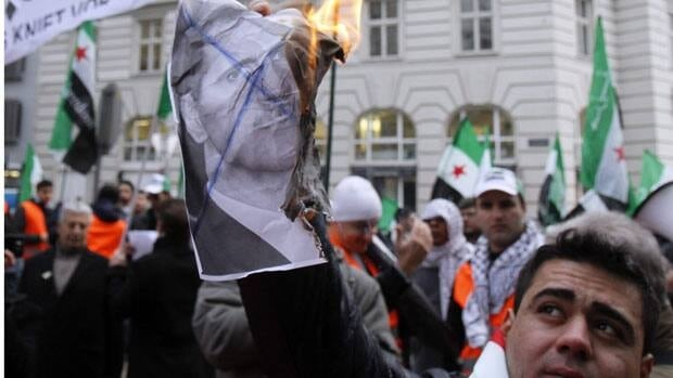 A protester holds up a burning picture of Syrian President Bashar al-Assad during a protest in Vienna, Austria, on Thursday.