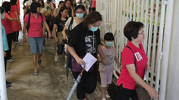 Parents meet at a Hong Kong school attended by a five-year-old boy who died of scarlet fever on June 21.