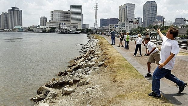 Rising waters lap the levee along the Moon Walk in New Orleans on Friday as some schoolchildren toss stones into the swollen Mississippi River.