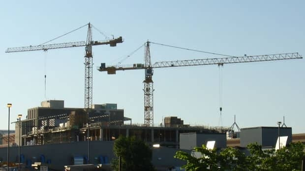 Construction cranes conduct work in Calgary. RBC Economics has cut its prediction for the pace of growth in the Canadian economy to 2.4 per cent.