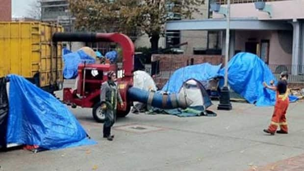 Victoria city workers brought a chipper and garbage truck to the Occupy Victoria camp at Centennial Square to help the protesters clean up the camp on Nov. 16. Protesters have been told to leave the area by 7 a.m. PT Saturday.