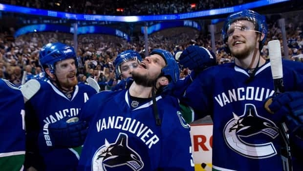 Vancouver Canucks' Kevin Bieksa, centre, who scored the game-winning goal, Alexander Edler, right, and Daniel Sedin, far left, celebrate after defeating the San Jose Sharks in the second overtime period of Game 5 on Tuesday in Vancouver.