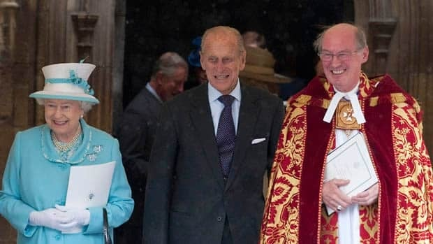 The Queen and her husband Prince Philip, centre, talk with the Dean of Windsor, David Conner, after a church service to mark the prince's 90th birthday in Windsor, west of London.