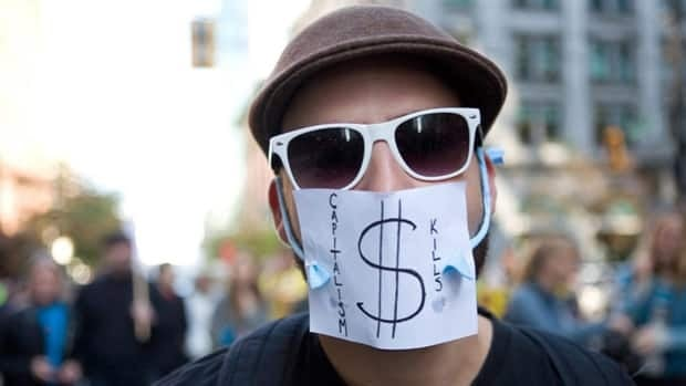 A masked protestor marches during the Occupy Vancouver group assembly in Vancouver, Saturday, Oct. 15, 2011.