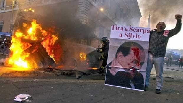 "A man standing next to a burning Carabinieri vehicle in Rome shows a placard depicting Italian Premier Silvio Berlusconi which reads ""Throw the shoe at Silvio"" in Italian. Protesters there hurled rocks and incendiary devices at police and banks."
