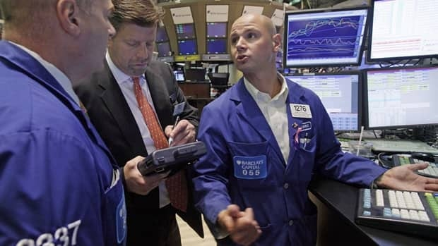 Mario Picone, right, talks with fellow specialist Evan Solomon, left, as trader Edward Schreier works on his handheld device, on the floor of the New York Stock Exchange.
