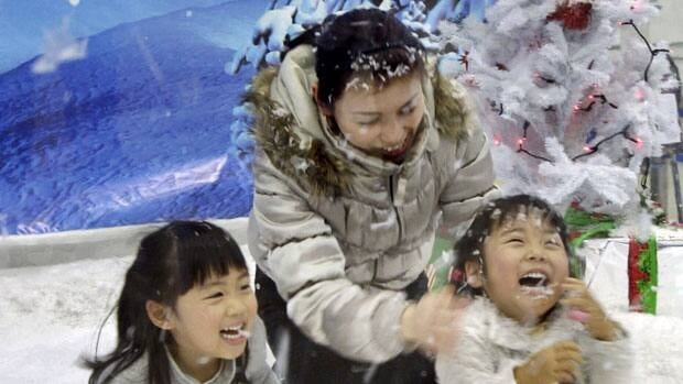 A Japanese family plays with artificial snow in a snow dome in Tokyo. Despite being hit with devastating natural disasters in 2011, Japan is the 23rd happiest country in the world, tied with Canada, according to a survey.