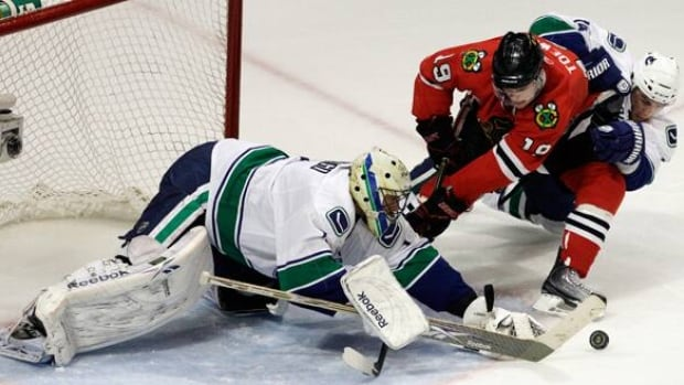 Vancouver Canucks goalie Roberto Luongo makes a save as Chicago Blackhawks centre Jonathan Toews (19) and Vancouver Canucks left wing Alex Burrows battle for the puck during the third period in Game 6 on Sunday. Luongo was called upon when starter Cory Schneider was injured during a penalty shot.