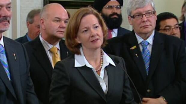 Alberta Premier Alison Redford listens to a question from a reporter in a news conference held after her new cabinet was sworn in.