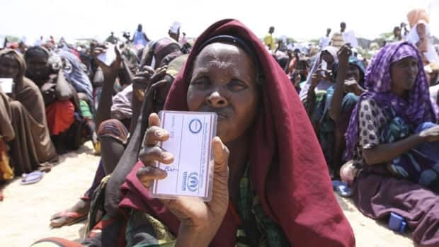 A woman at a refugee camp in Somalia holds up her food pass as she waits in a food distribution line in August. On Wednesday, October 26, 2011, Canada announced $350 million in new food aid funding.