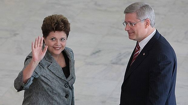 Prime Minister Stephen Harper, right, looks on as Brazilian President Dilma Rousseff waves to journalists upon Harper's arrival at the Planalto palace in Brasilia, Brazil, Monday, Aug. 8, 2011. Harper is on a three-day visit to Brazil.