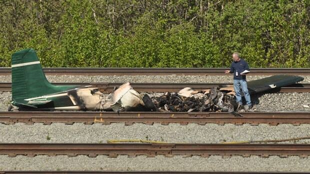 A U.S. National Transportation Safety Board official investigates the scene of a plane crash near Anchorage, Alaska, on Friday. Five people were killed when a small airplane crashed shortly after takeoff from a suburban Anchorage airport.