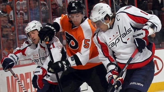 Braydon Coburn of the Flyers struggles to control the puck against Brooks Laich, left, and Alex Ovechkin, right, of the Capitals. Washington used a three-goal third period to top the Flyers 5-2.