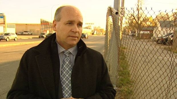 Chamber of Commerce president Dave Angus stands alongside the chain-link fence that lines Route 90.