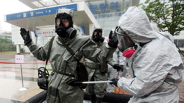 South Korean military soldiers wearing anti-chemical suits check mock chemical pollutants on others during a chemical attack drill Tuesday in Namyangju, north of Seoul, South Korea.