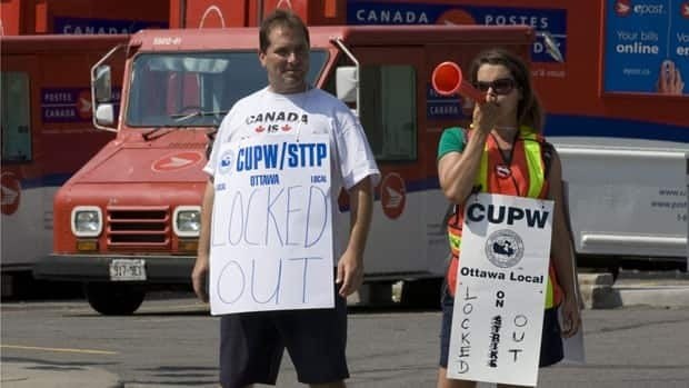 Canada Post trucks are parked behind workers demonstrating outside a sorting facility in Ottawa on June 15, 2011 after the corporation locked them out.