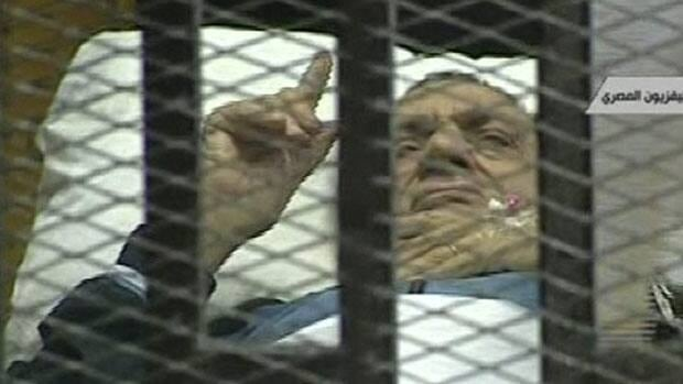 Former Egyptian president Hosni Mubarak gestures in this video images as he lies on a bed within a cage at the court building in Cairo on Monday as his trial on charges of corruption and complicity in killing protesters during Egypt's uprising continued.