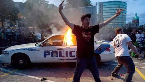 Vancouver Canucks fans pose in front of a burning police cruiser during the Stanley Cup riot in downtown Vancouver on June 15, 2011.
