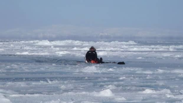 David Alexander sits on his floating sled and some empty gas cans as he awaits rescue near the mouth of Frobisher Bay. A helicopter arrived three and a half hours later.