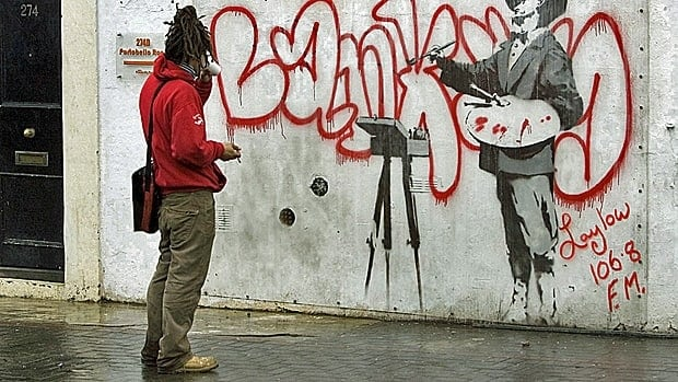 An admirer takes in graffiti by British artist Banksy. Smart businesses need to think outside the box to get notices, experts say.